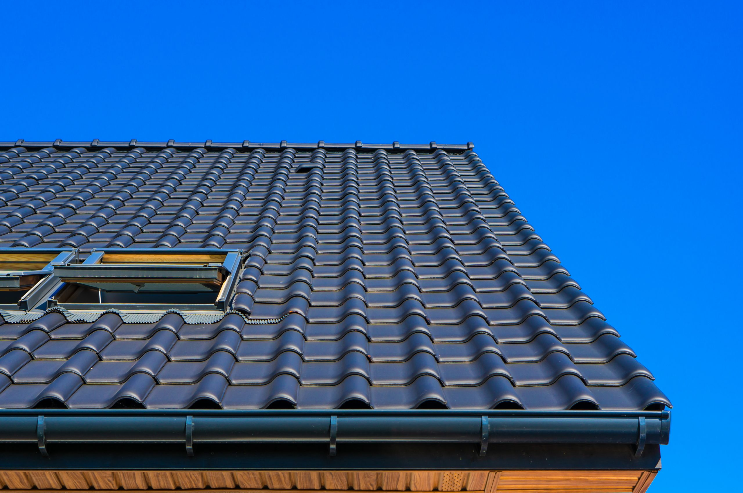 A vertical low angle closeup shot of the black roof of a building with a blue background